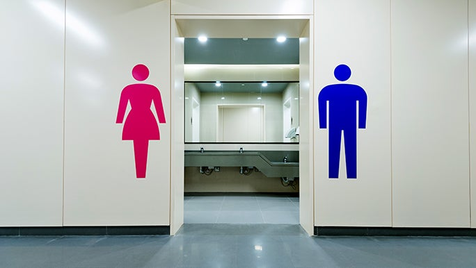 The doorway of a unisex bathroom, there is a large sticker of a lady one on the left side and man on the right.