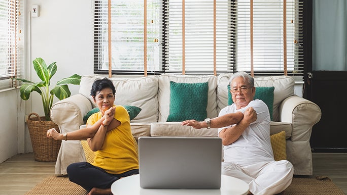 couple sits on the floor in front of a couch. There's a coffee table with an open laptop in front of them. They look to be doing some sort of guided workout.