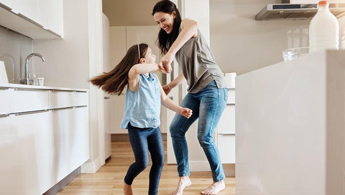 A woman and child are partaking in a mood boosting dance session. They are holding hands and smiling.