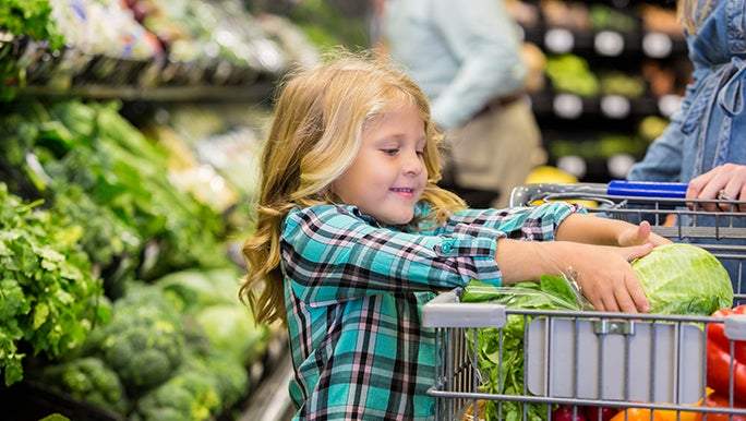 Little girl helping her female caregiver shop for produce in the grocery store, she is putting an iceberg lettuce in the trolley.