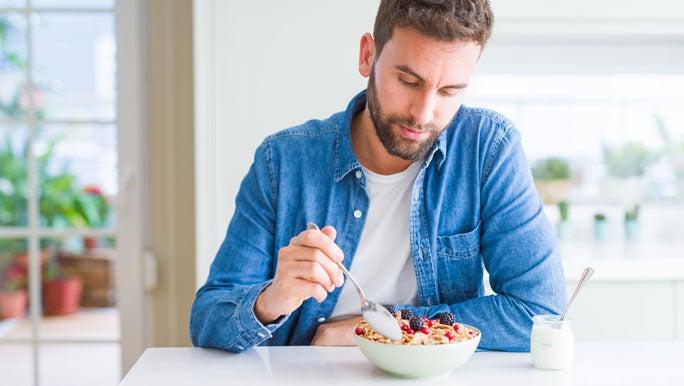 Man eating a healthy breakfast of muesli, berries and yogurt in his kitchen