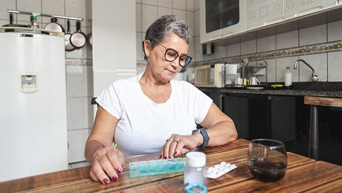 Woman with short salt and pepper hair, glasses and hot pink nails sitting at a wooden kitchen table. There is a pill box and drink on the table, she is looking at her watch.