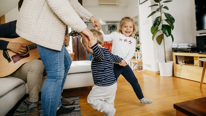 A family is dancing in their home, dad is playing the guitar. Music and health are so closely related.