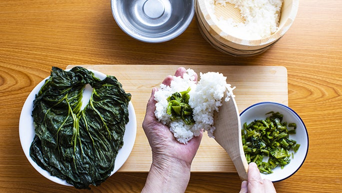 From above, someone prepares pickled leaves (T A K A N A) wrapped in rice.