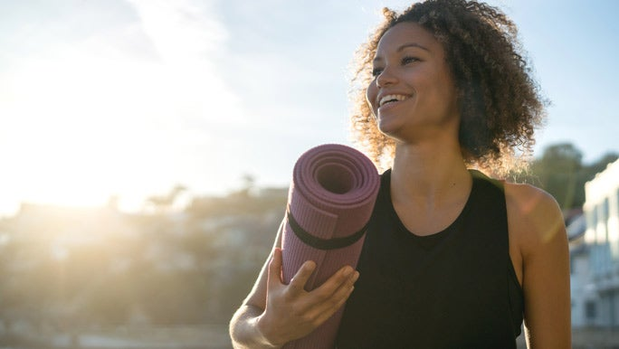 Smiling woman in black active wear holding a rolled up purple yoga mat