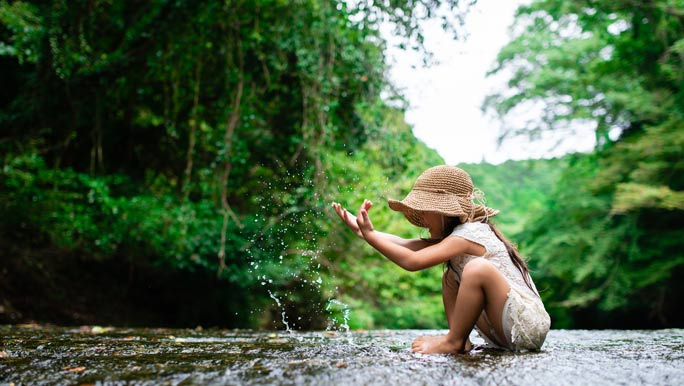 Young girl having fun and playing in the water in the bush