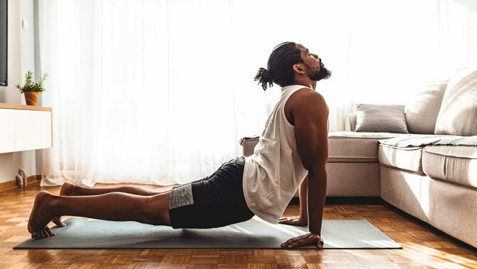 Man doing yoga at home he is in upward facing dog yoga pose