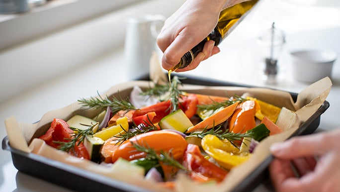 On a white kitchen bench, a tray of veggies fresh out of the oven is cooling.