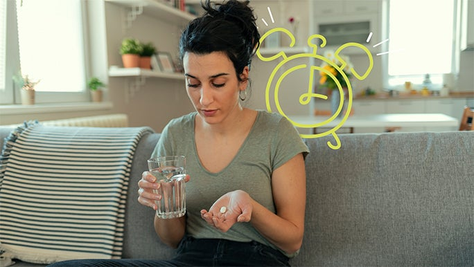 Woman sitting on the couch with a glass of water to take her medication
