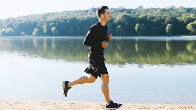 A man wearing all black is jogging next to a lake, he is enjoying the health benefits of running.