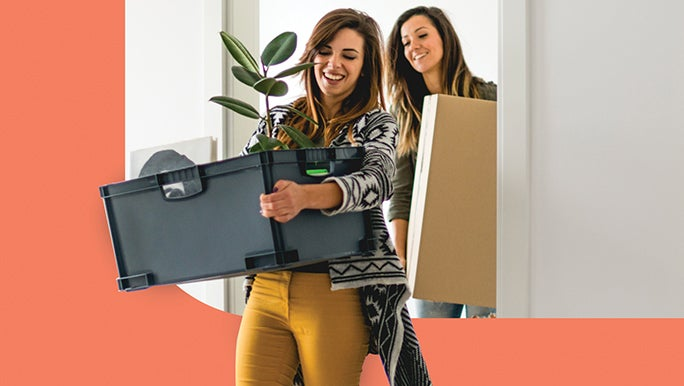 Female couple carrying moving boxes
