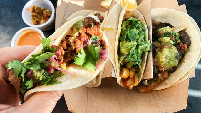 A hand holding some healthy looking takeaway tacos. They are full of veggies and herbs.