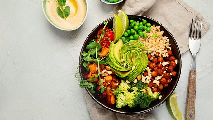 Top view of a bowl of mixed grilled vegetables on a light background with squeezed limes scattered around. Brain healthy foods galore!