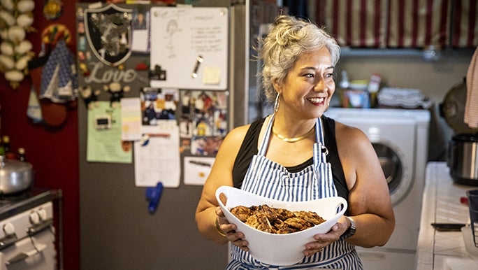 A smiling woman wearing a striped apron carries a bowl of food for a weekly family meal.