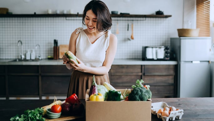Smiling woman in the kitchen unpacking a box of fresh produce