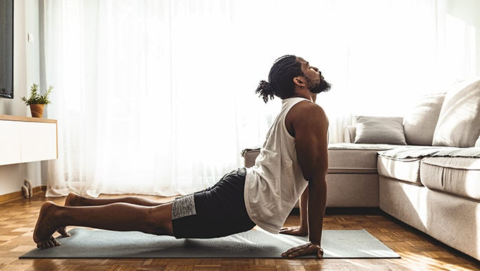 A man practices yoga in his home. He is in cobra pose.