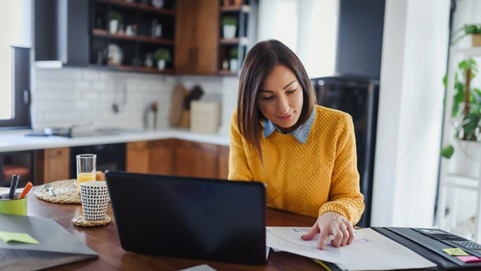A woman works from a desk in her home, she looks happy and productive.