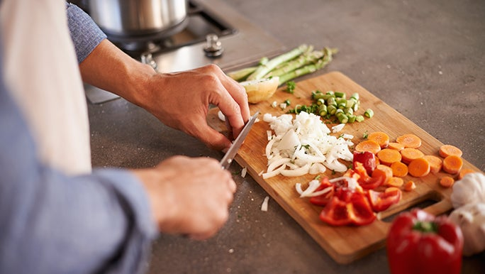 A man chops onions, carrots and capsicum on a wooden chopping board. He may be following a gut heath diet.
