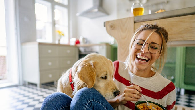 A lady sits on the floor of her kitchen eating something colourful out of a bowl. Her dog is trying to get in on the action.