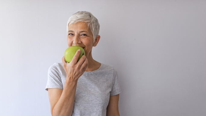 A lady is enjoying an apple, she is choosing healthy food over a fad diet.