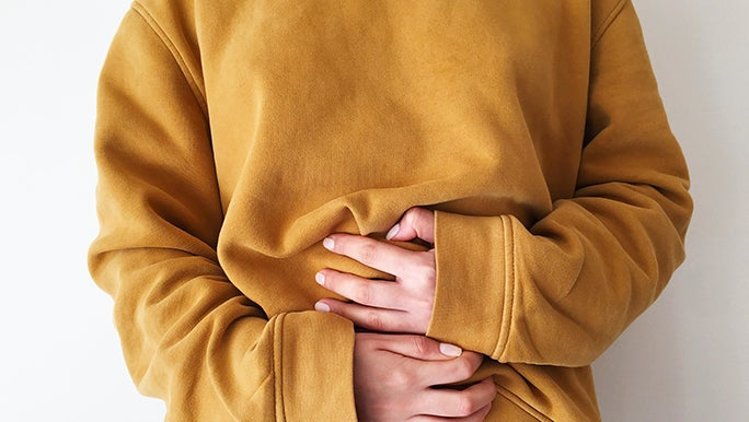 Up close, the torso of a woman wearing a mustard-coloured jumper is in the center of the frame. She is holding her gut in a way that suggests she's experiencing bowel problems.