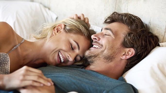A man and woman are laying on their backs as they're in bed. They're cuddling each other and smiling, as she lays her head on his shoulder and one hand on her head. Whilst both holding hands with the other, representing a healthy sex life.