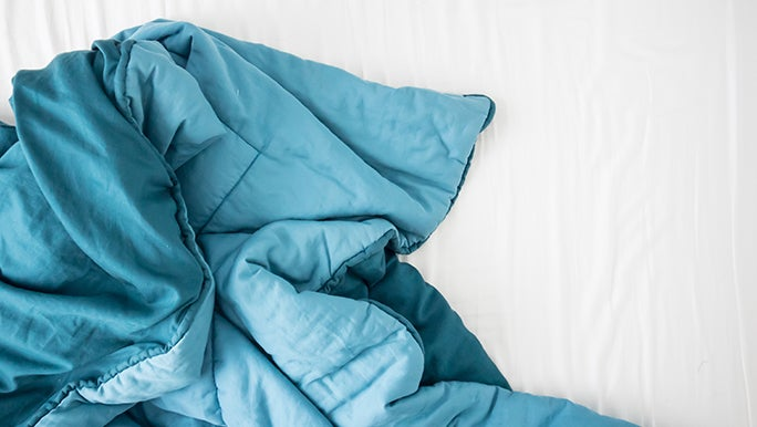 From above, a blue weighted blanket is crumpled up on a white sheet.