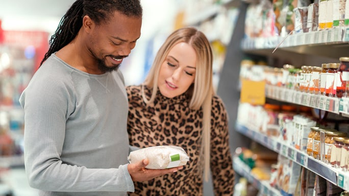 A man and woman are at the grocery store and standing In the middle of the aisle, reading the food labels, so they know which foods to avoid when you have a wheat allergy.