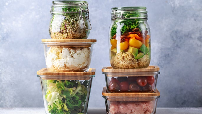 Glass containers of all different kinds are stacked on top of each other. They all have cooked veggies in them.