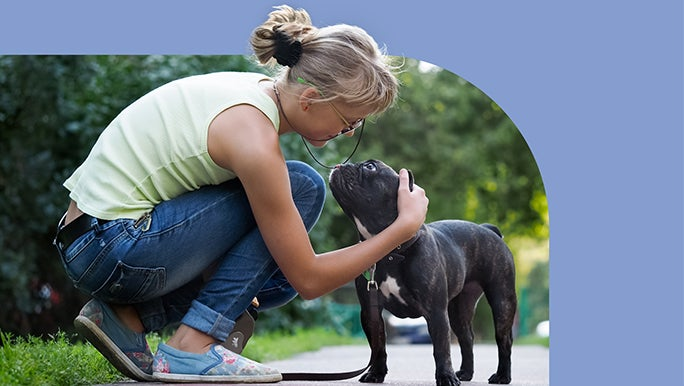 Woman crouching down to pat her dog while out walking