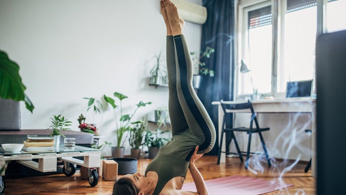 Woman practices Yoga in her home.