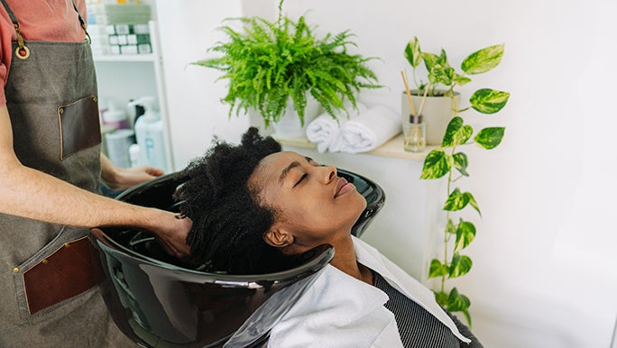 A lady leans back and enjoys having her curly hair shampooed in a salon sink.