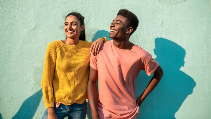 A couple in bright clothing are standing in front of a green rendered wall. They are currently enjoying the love language of quality time.