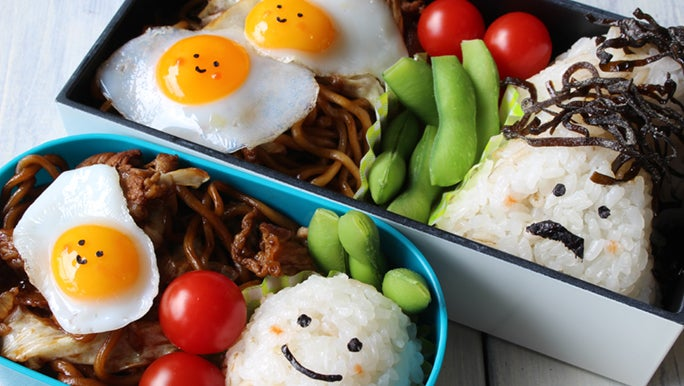 A cute, bento style lunch box with a rice ball, fried egg and noodles.
