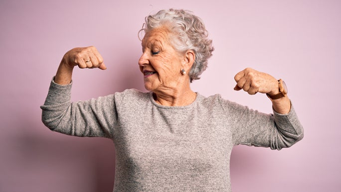 A healthily ageing woman is flexing her muscles and smiling in front of a purple wall.