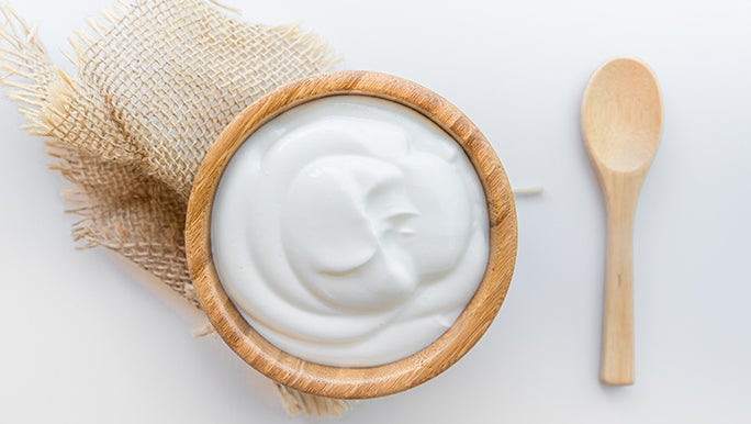 From above, a wooden bowl filled with yoghurt (a fermented food) is sitting on a white table next to a wooden spoon.
