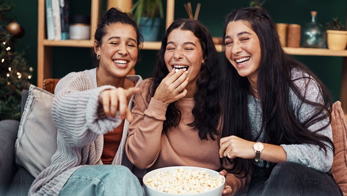 3 young ladies are sitting down eating popcorn, as they enjoy watching a movie. Some could say farts smell similar to popcorn.