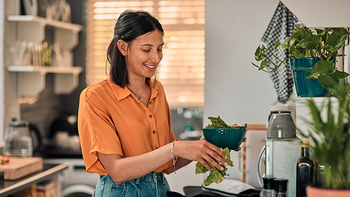 A smiling woman looks down on the piece of lettuce she is washing at the sink and knows that it's not about 'fixing' gut health but finding what works for her.