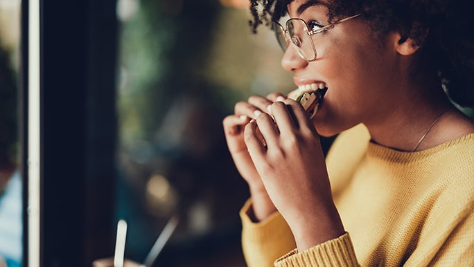 A woman is enjoying a piece of bread because improving gut health doesn't mean you have to remove food such as bread.