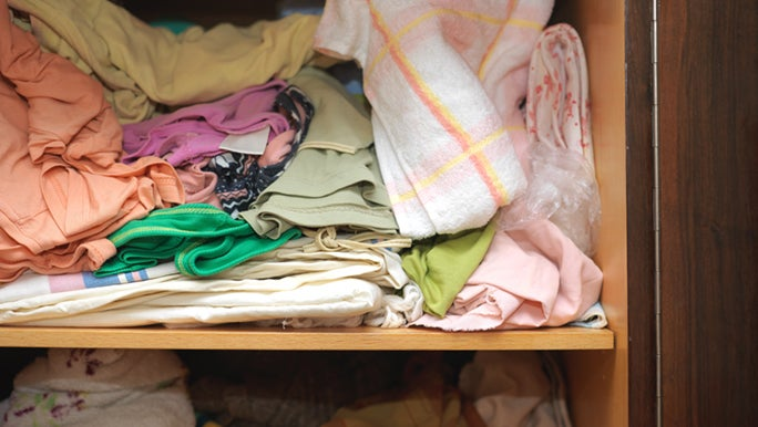 A close-up view point of a linen closet that has not been decluttered in a LONG time.