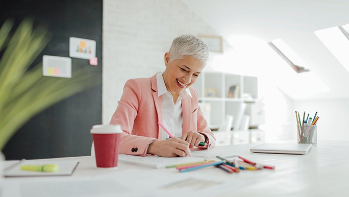 A woman in a bright office smiles as she does her work with colourful markers.