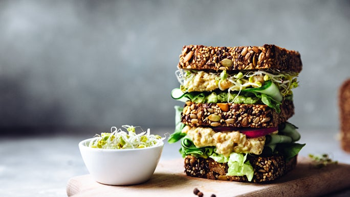 A whole grain sandwich is stacked on a breadboard. This type of food is better for gut health.