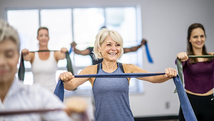 A smiling woman enjoys a group exercise class, she is holding a resistance band in front of her chest.