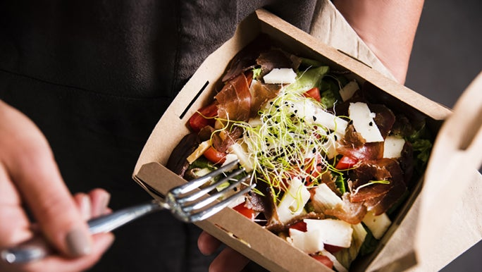 A fork is digging into a healthy takeaway salad full of sprouts, feta and tomatoes.