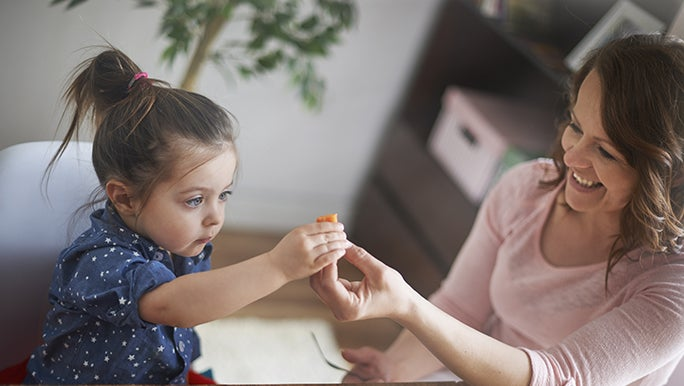Kids can develop a healthy relationship with vegetables like this child looking curiously at a piece of vegetable that her mum is handing to her.