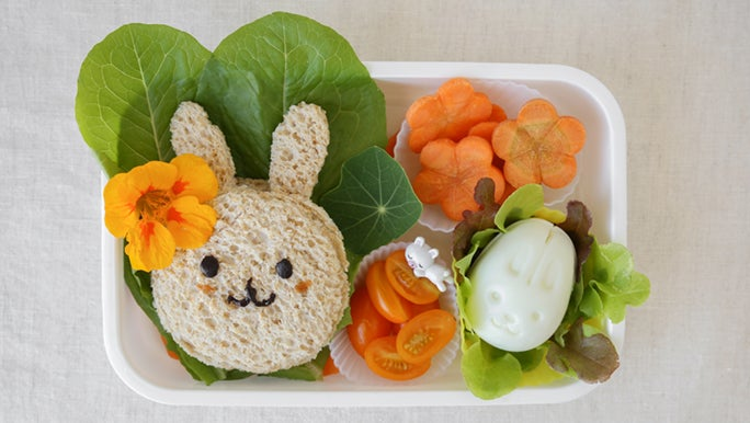 From above, an open lunch box containing a sandwich shaped like a rabbit and fresh, chopped veggies. It seems as though it may have been prepared for a fussy toddler.