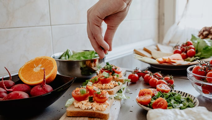 Someone sprinkles herbs over some healthy open sandwiches in a modern kitchen.