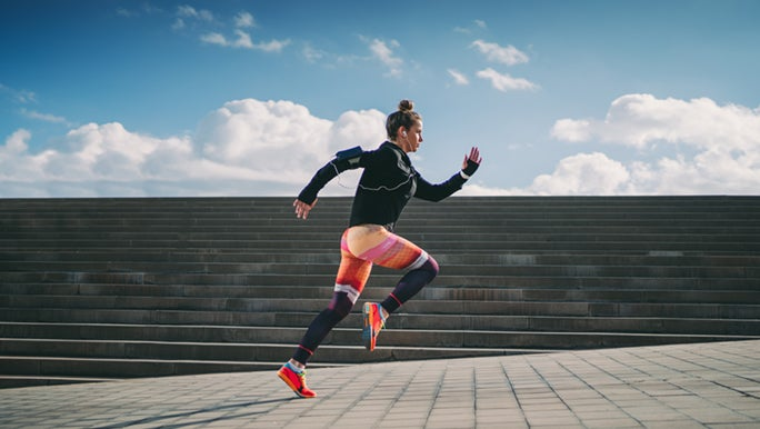 From the side, a woman wearing bright activewear sprints up a concrete slope. There are concrete stairs behind her and above them, a blue sky.