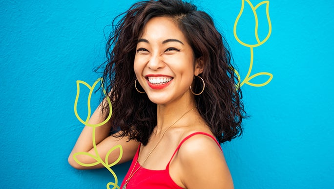 Happy young woman smiling  in a red top in front of a blue wall
