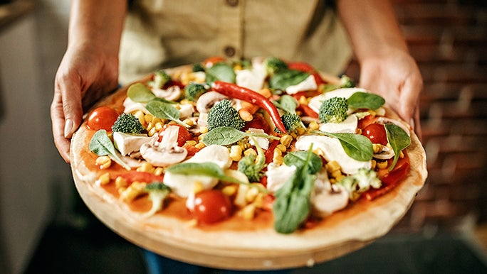 Two hands hold a pizza that's covered in mushrooms, broccoli, tomato and spinach.